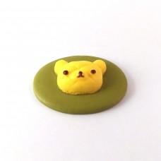 The head of a bear on a green oval